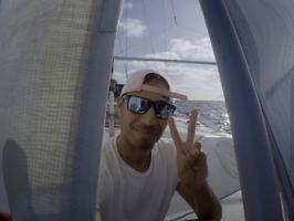 sailor at the bow of a catamaran crossing the Atlantic